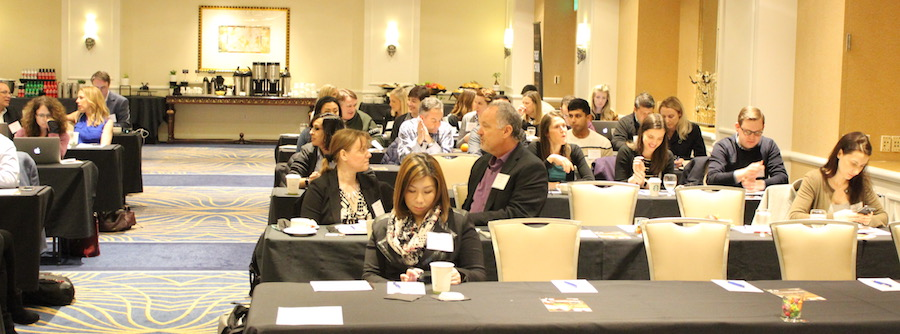 Attendees at a Customer SuccessCon event, seated at tables