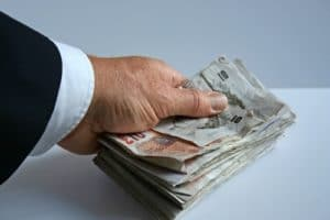 A hand holding a large stack of money