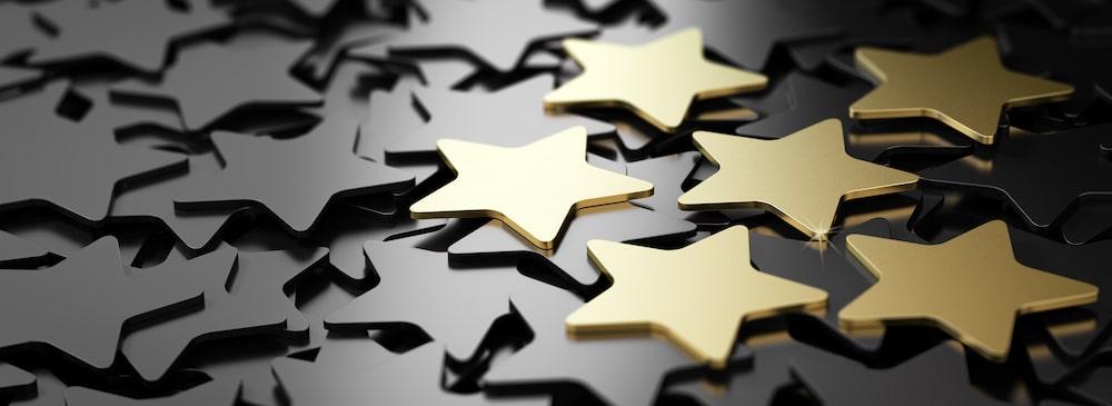 Six golden stars over black background.