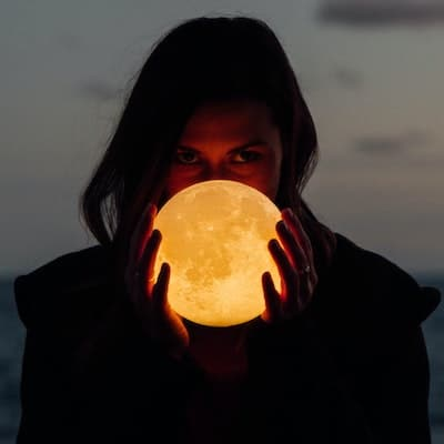 Iamge of woman holding the moon as a crystal ball in her hands