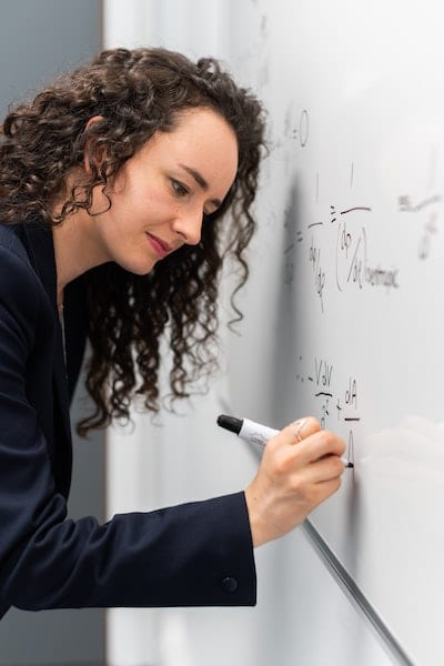 Image of business woman doing math on a whitboard