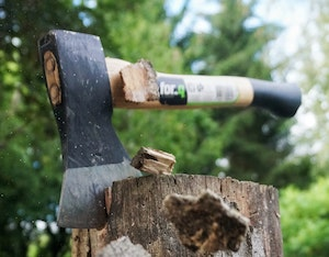 Axe head sunk into wood stump with flying chips