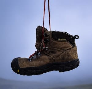 Image of a boot hanging by the laces in air