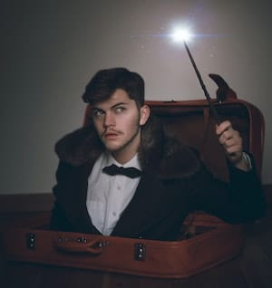 Magician holding wand coming up from open suitcase